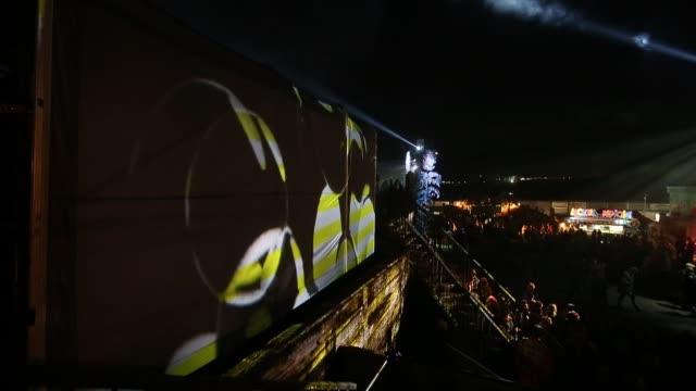 People walk around The Common a late night venue at the Glastonbury Festival at Worthy Farm Pilton on June 27 2015 in Glastonbury England