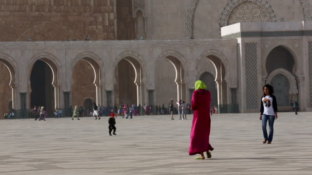 people walk around the hassan ii mosque in casablanca 2 - モロッコ文化点の映像素材/bロール