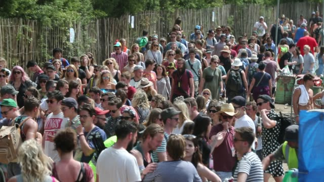 people walk around the site at the glastonbury festival at worthy farm, pilton on june 27, 2015 in glastonbury, england. - お祭り好き点の映像素材/bロール