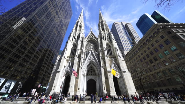 people walk around the st. patrick's cathedral among the midtown manhattan skyscrapers at new york ny usa on apr. 21 - st. patrick's cathedral manhattan stock videos and b-roll footage