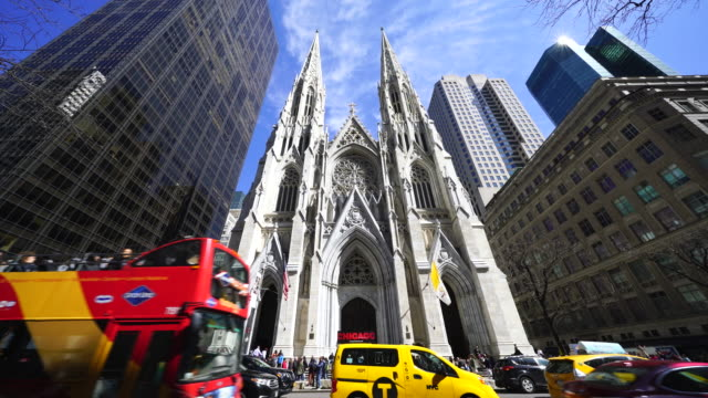 people walk around the st. patrick's cathedral and cars go through fifth avenue among the midtown manhattan skyscrapers at new york ny usa on apr. 21 - st. patrick's cathedral manhattan stock videos and b-roll footage