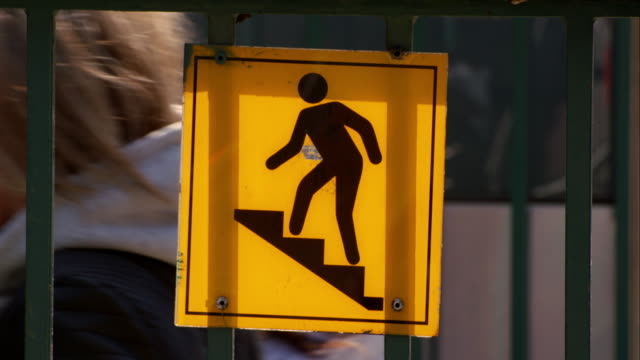 People walk by a caution sign for stairs going into the subway.