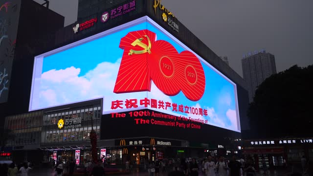 people walk by a large 3d screen showing an advertisement for the 100th anniversary of the founding of the communist party of china on june 21, 2021... - kommunismus stock-videos und b-roll-filmmaterial
