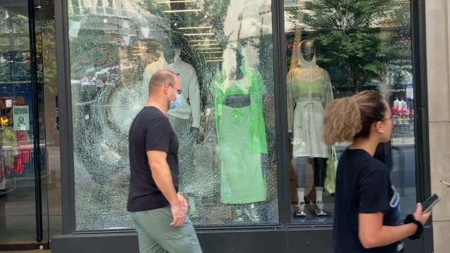 people walk by and take photos of a window shattered at a clothing store along michigan avenue after it was looted on august 10, 2020 in chicago,... - other stock videos & royalty-free footage