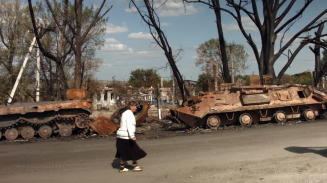ws people walk by destroyed military equipment from a recent battle outside of the battered city of lugansk on september 13 2014 in lugansk ukraine... - ukraine stock-videos und b-roll-filmmaterial