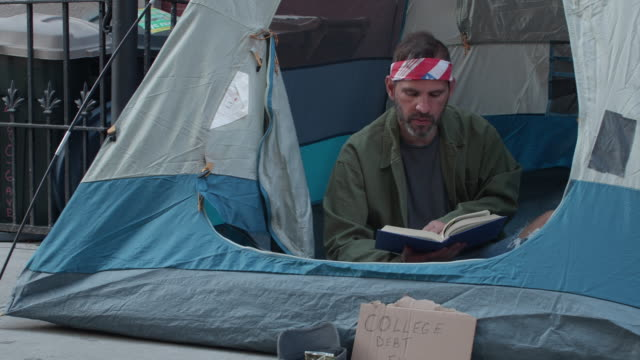 ms people walk by homeless man reading book in tent - 放浪者点の映像素材/bロール