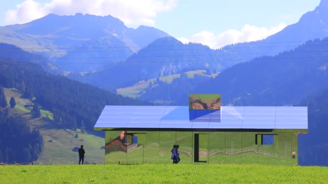 people walk by mirage gstaad by los angelesbased artist doug aitken is on display outside as installation sculpture representing a chalet made with... - ski resort stock videos & royalty-free footage