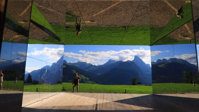 "people walk by ""mirage gstaad"" by los angeles-based artist doug aitken is on display outside as installation sculpture representing a chalet made... - kaleidoscope pattern stock videos & royalty-free footage"