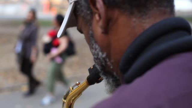 stockvideo's en b-roll-footage met people walk by old street performer playing saxophone in new york city park - saxofonist