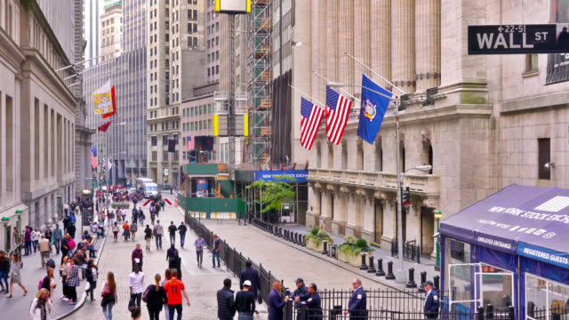 people walk by stock market exchange on wall street. american flag. - exchanging stock videos & royalty-free footage