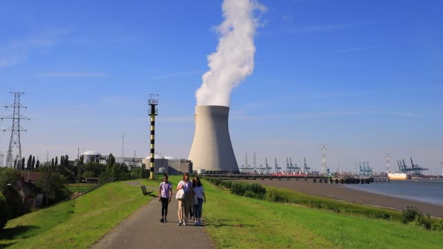 stockvideo's en b-roll-footage met people walk by the cooling towers of doel nuclear plant on july 13, 2020 in beveren, belgium. doel power station under the authority of electrabel... - straling