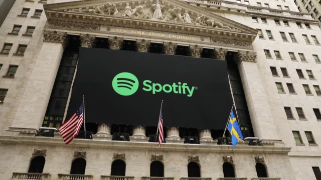 people walk by the new york stock exchange on the morning that the music streaming service spotify begins trading shares at the nyse on april 3, 2018... - spotify stock videos & royalty-free footage