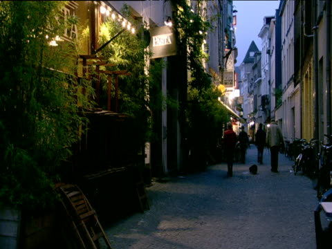 people walk dog down cobbled alley past shop fronts houses and pasta restaurant antwerp - cobblestone stock videos & royalty-free footage