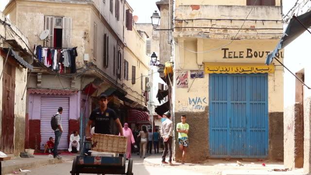people walk down a neighborhood street in casablanca - old town stock videos & royalty-free footage