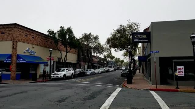 people walk down main street on a foggy day in martinez, california, january 10, 2019. - targa con nome della via video stock e b–roll