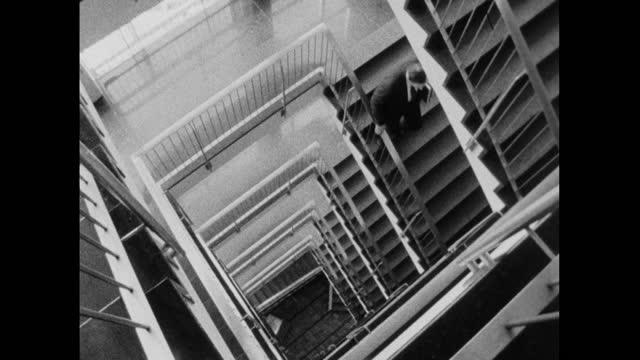 people walk down stairs and along corridors in office building; 1964 - sekretärberuf stock-videos und b-roll-filmmaterial