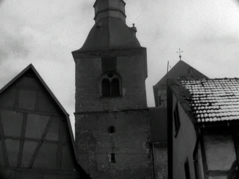 people walk down steps near a church in remagen. 1955. - kirchturmspitze stock-videos und b-roll-filmmaterial