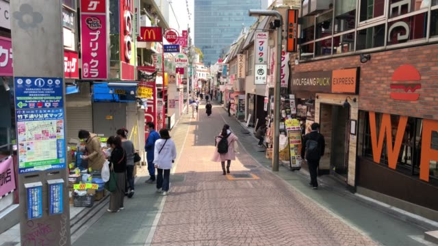vídeos de stock e filmes b-roll de people walk down takeshita street where most of the shops have closed because of the state of emergency imposed yesterday, on april 8, 2020 in tokyo,... - epidemia