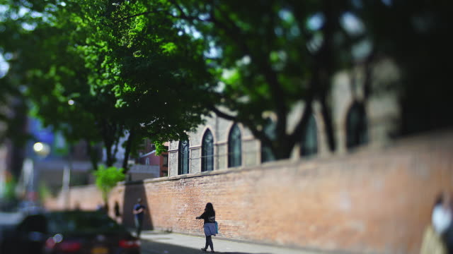vídeos de stock, filmes e b-roll de people walk down the sidewalk along the brick wall of the basilica of st. patrick's old cathedral under the big trees in the nolita district at new york city ny usa on may 22 2019. - tilt shift