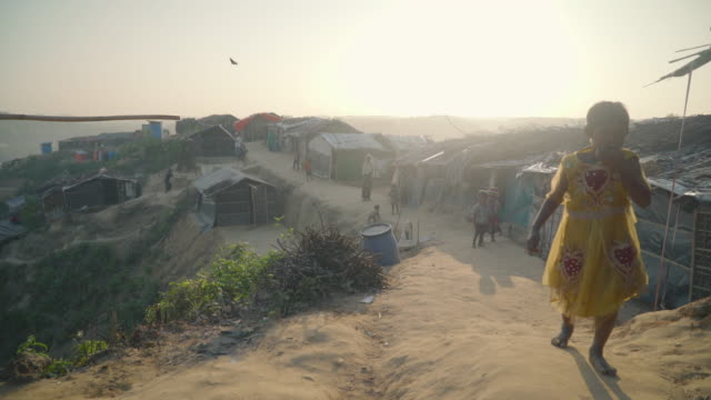 People walk down walkway by their homes in Kutupalong refugee camp in Bangladesh at sunset along a high ridgeline Fleeing persecution by the Myanmar...