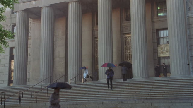 vídeos de stock, filmes e b-roll de people walk in and ouf of new york courthouse with umbrellas as it rains. - forma da água