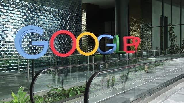 people walk in front of a sign featuring google inc's logo at the company's asia pacific headquarters during its opening day in singapore on thursday... - ロゴマーク点の映像素材/bロール