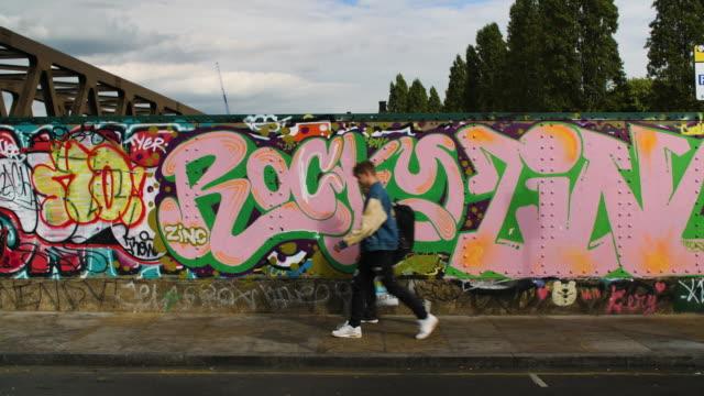 people walk in front of colourful graffiti on brick lane - street style点の映像素材/bロール