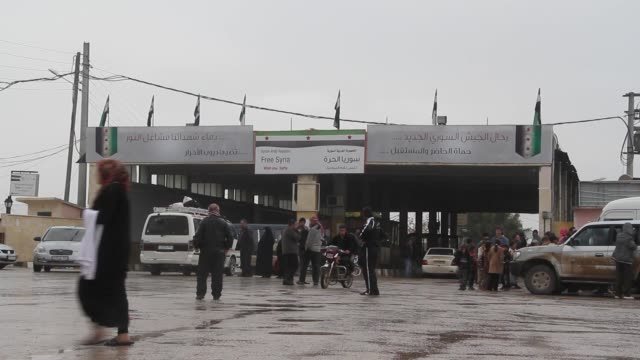 people walk in front of the border crossing near the bab al-salam syrian refugee camp near in azaz syria on the border with turkey. - 国境点の映像素材/bロール