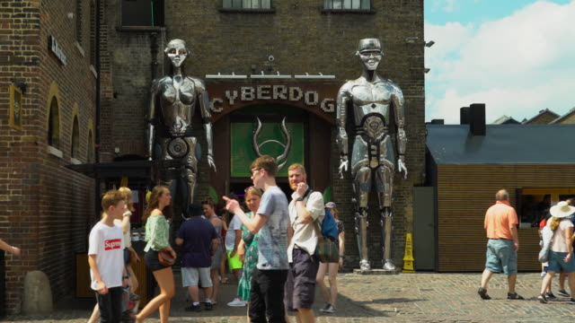 People walk in front of the entrance to Cyberdog in Camden Market, London