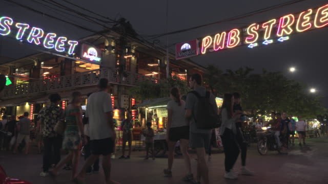 pan / people walk in pub street at night in downtown siem reap - nachtmarkt stock-videos und b-roll-filmmaterial