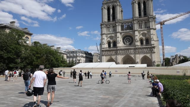 people walk in the square of notre dame cathedral on pentecost sunday on may 31, 2020 in paris, france. almost one year after fire ravaged the... - ペンテコステ点の映像素材/bロール
