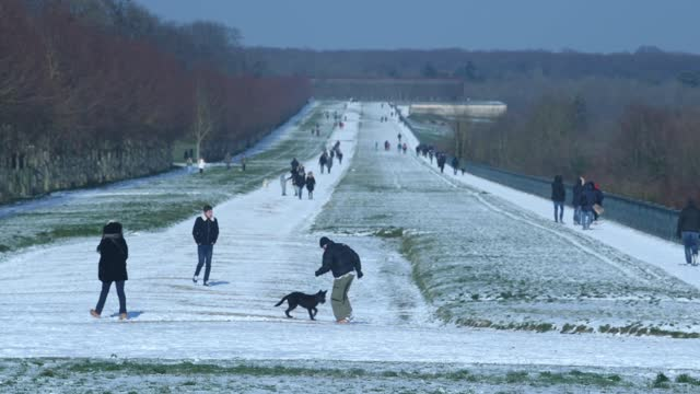 people walk in the terrasse gardens covered in snow following a light overnight snowfall on february 10, 2021 in saint germain en laye, france. the... - snowing stock videos & royalty-free footage
