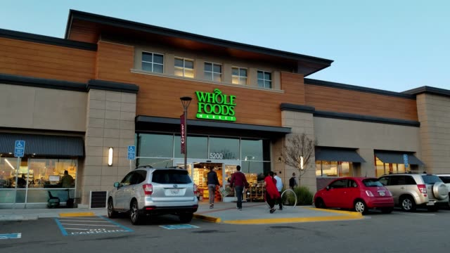 people walk into the whole foods market grocery store in dublin california at night as cars pass by april 2 2018 - whole foods market stock videos and b-roll footage