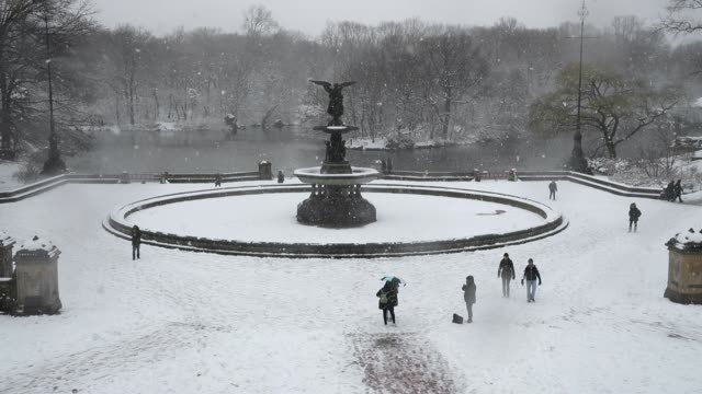 vídeos de stock, filmes e b-roll de people walk near the bethesda fountain in central park during a snowstorm march 21 2018 in new york city the fourth nor'easter of the month hit the... - atlântico central eua