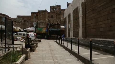 people walk near the buildings of the historic old quarter of sana'a still standing as recent rains have threatened the city's heritage sites through... - unesco world heritage site点の映像素材/bロール