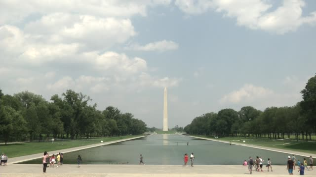 people walk near the lincoln memorial reflecting pool it is the largest of the many reflecting pools in washington dc united states it is a long and... - washington monument stock videos & royalty-free footage