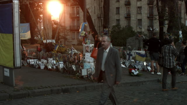 ws people walk near tributes to ukrainian protesters who were killed during demonstrations in independence square or maidan square on september 5... - ukraine stock-videos und b-roll-filmmaterial