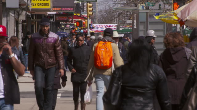 vídeos de stock, filmes e b-roll de people walk on a a busy sidewalk in harlem on broadway and 137st in slow motion. - 2016
