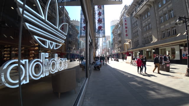 people walk on a business street wearing face masks for the covid19 epidemic situation is much better in china more and more people go on street... - chinese ethnicity stock videos & royalty-free footage