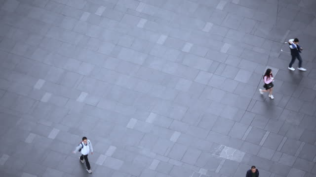 people walk on across the pedestrian concrete landscape in the city street (aerial top view) - schlagschatten stock-videos und b-roll-filmmaterial