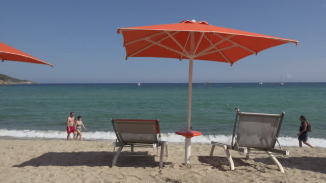 people walk on beach with sunshade and deck chairs - island of elba stock videos & royalty-free footage