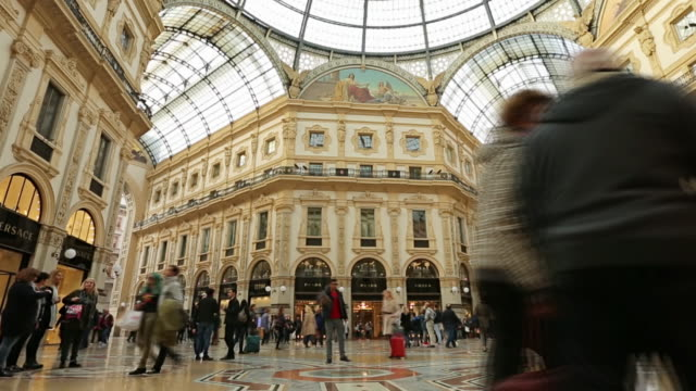 People walk on Duomo square near the famous Vittorio Emanuele shopping gallery, Milan city, Italy.