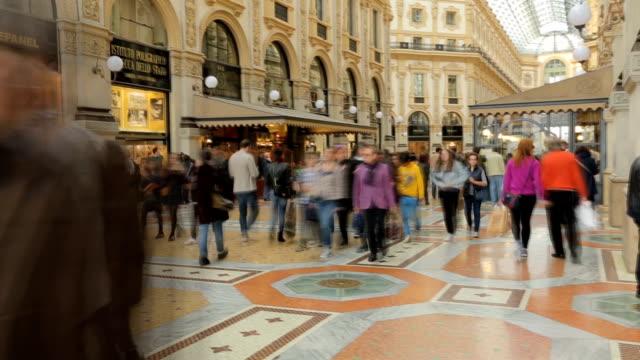 vídeos de stock, filmes e b-roll de as pessoas andam na praça duomo, perto da galeria comercial famosa vittorio emanuele, a cidade de milão, itália. - dentro