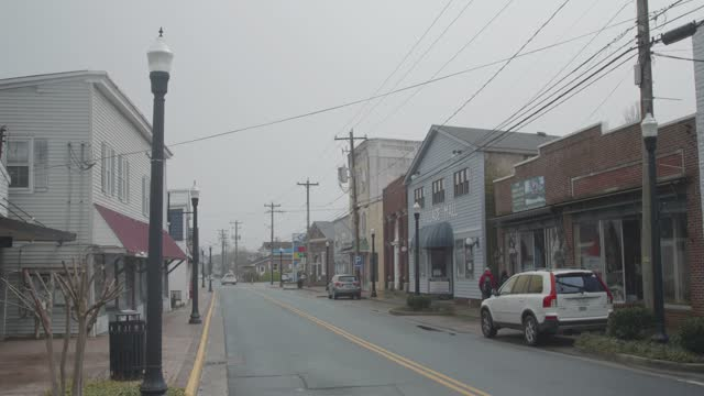 people walk on main street amidst pandemic related restrictions on march 28, 2021 in chincoteague, virginia. there have been 546,299 covid-19 deaths... - street name sign stock videos & royalty-free footage