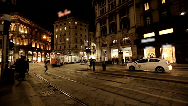 People walk on Milan city traffic by night.