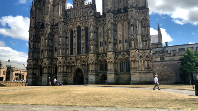 people walk on parched grass as they visit wells cathedral in wells on july 24, 2018 in somerset, england. the lack of rainfall over the last few... - wells cathedral stock videos & royalty-free footage