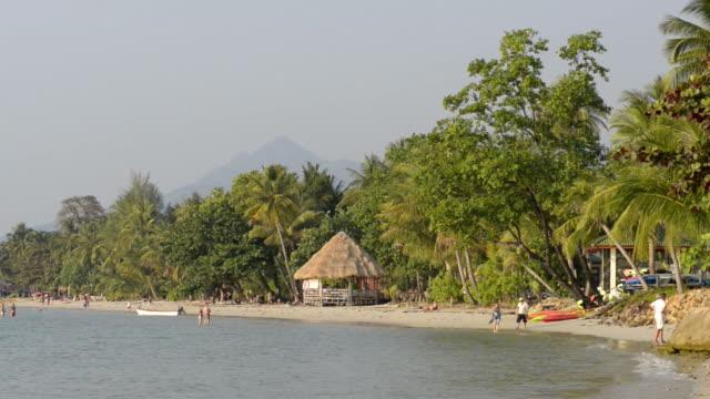 people walk on sandy beach with beach gazebo - tetto di paglia video stock e b–roll