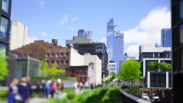 vídeos de stock, filmes e b-roll de people walk on the highline park promenade toward the hudson yards high-rise buildings, which promenade is surrounded by fresh green trees and plants in spring season at new york city ny usa on may 15 2019. - tramway