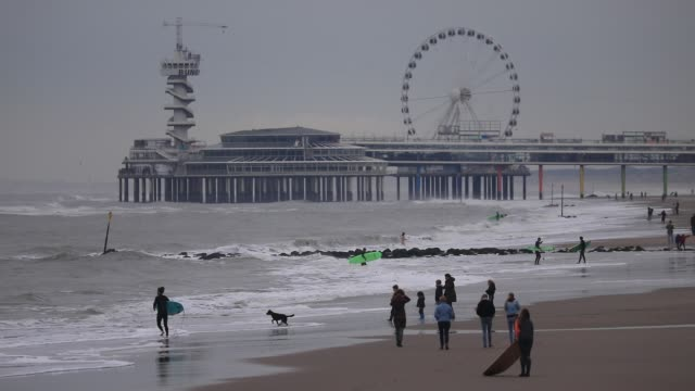people walk on the sand by the north sea, the scheveningen with a pier in the background on october 19, 2020 in the hague, the netherlands. for a few... - silver coloured stock videos & royalty-free footage