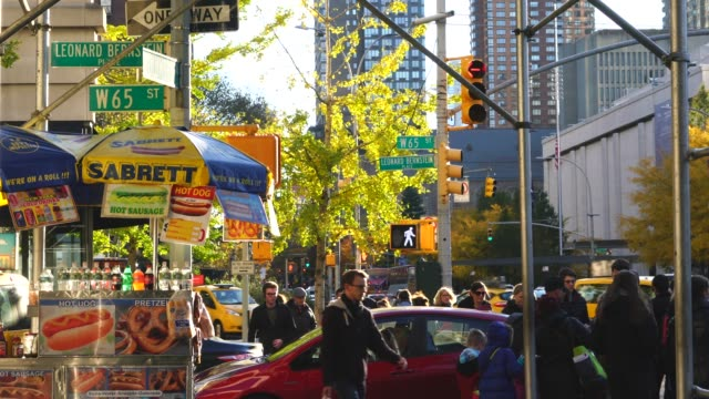 people walk on the sidewalk beside the hot dog stand at upper west manhattan at new york ny usa on nov. 17 2018. - autumn stock videos & royalty-free footage